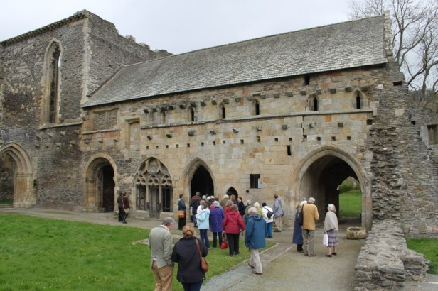 Brian and Moira Gittos with the Cambrians looking at the east range of the cloister at Valle Crucis Abbey